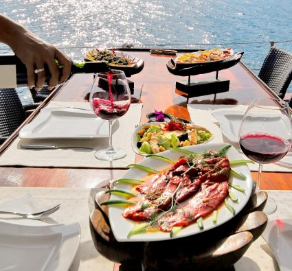 wine glasses and dinner setting on table by the water