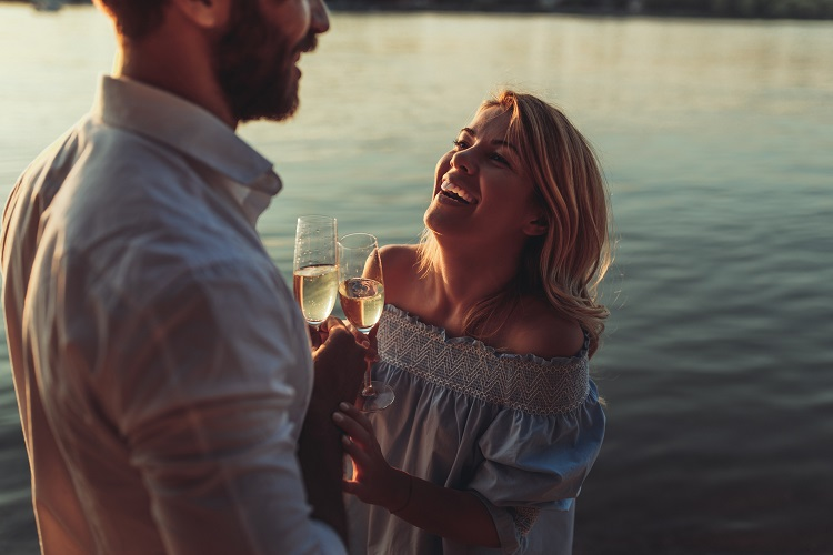 Couple enjoying champagne by the water