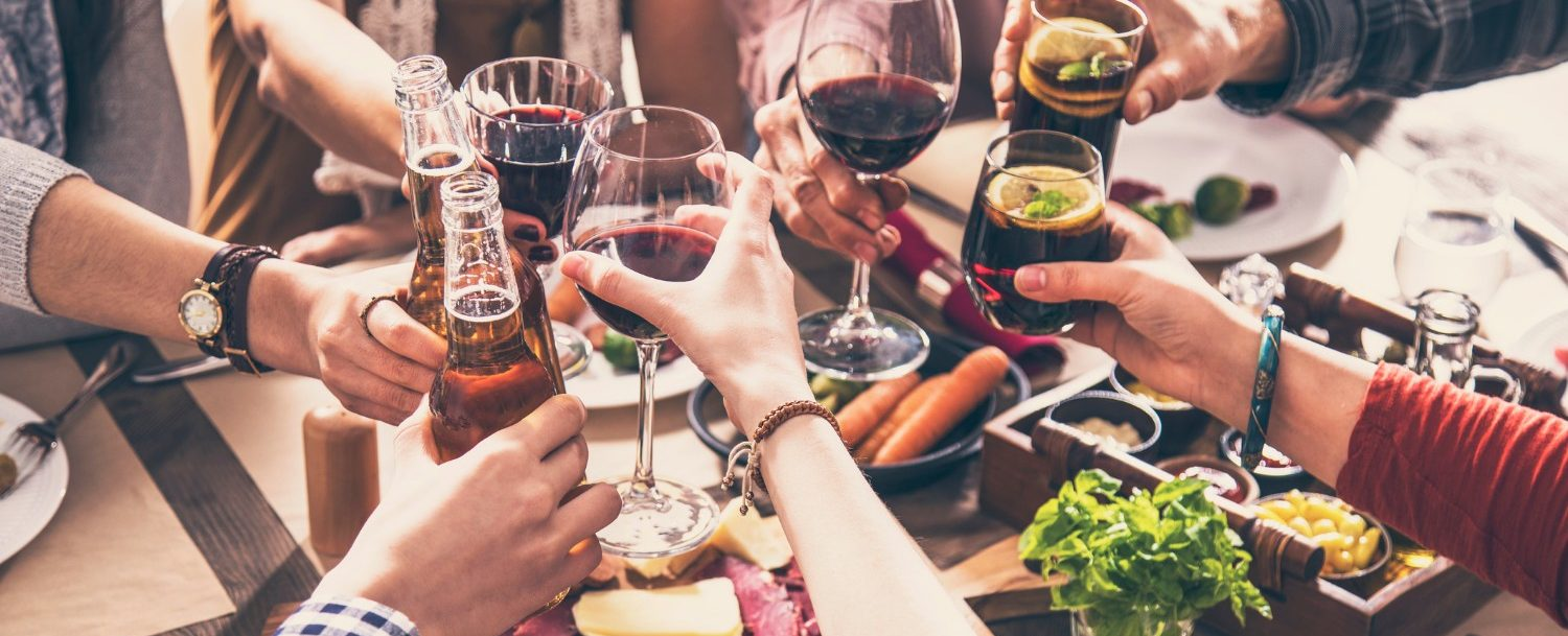 friends sharing wine and cheese and meat plates at a table