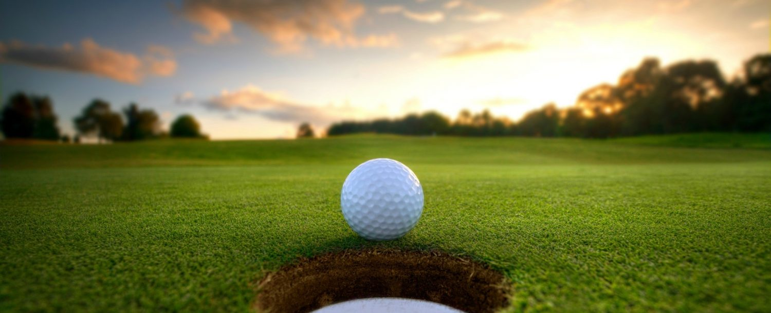 Golf ball rolling into hole at sunset