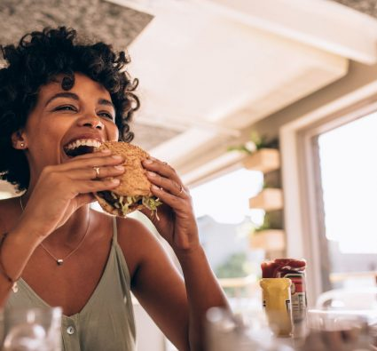 Woman Eating Burger at Hip Restaurant