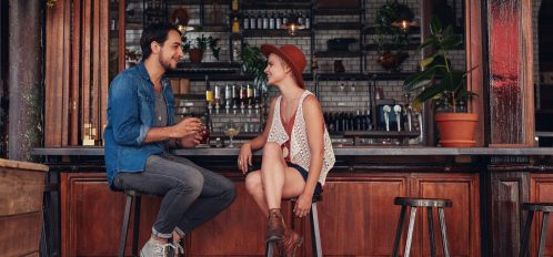 Shot of young couple sitting at cafe counter. Young man and woman at bar